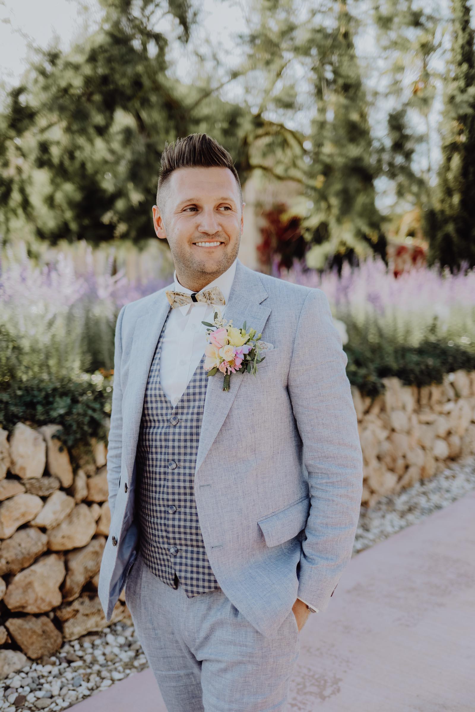 Bräutigam in blauem Anzug mit Blumenanstecker