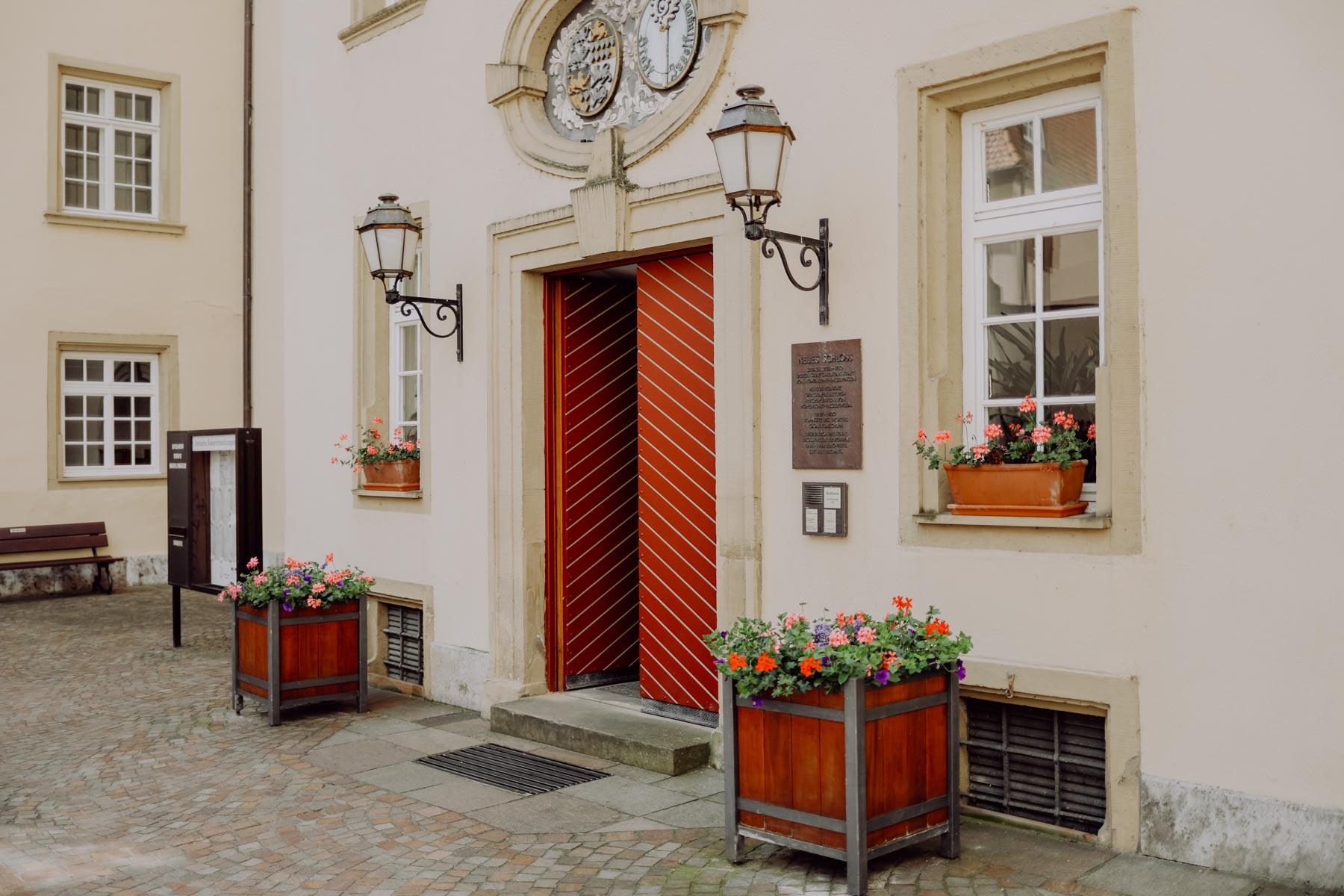 Eingang mit Blumenkübeln und Laternen am Haus