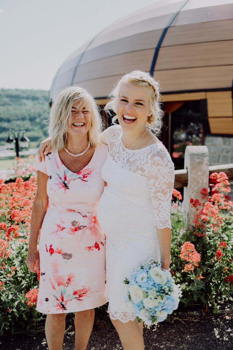 Zwei Frauen lachen vor roten Blumen