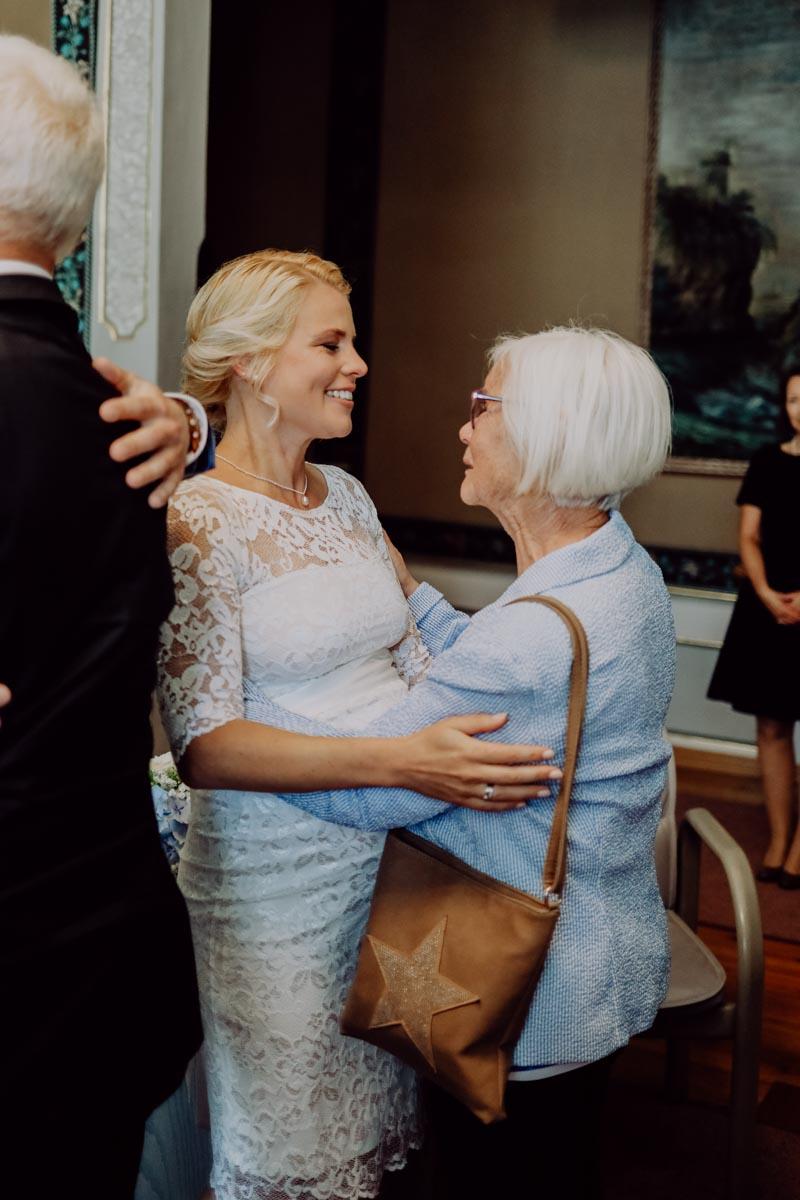 Braut umarmt Frau mit blauem Oberteil
