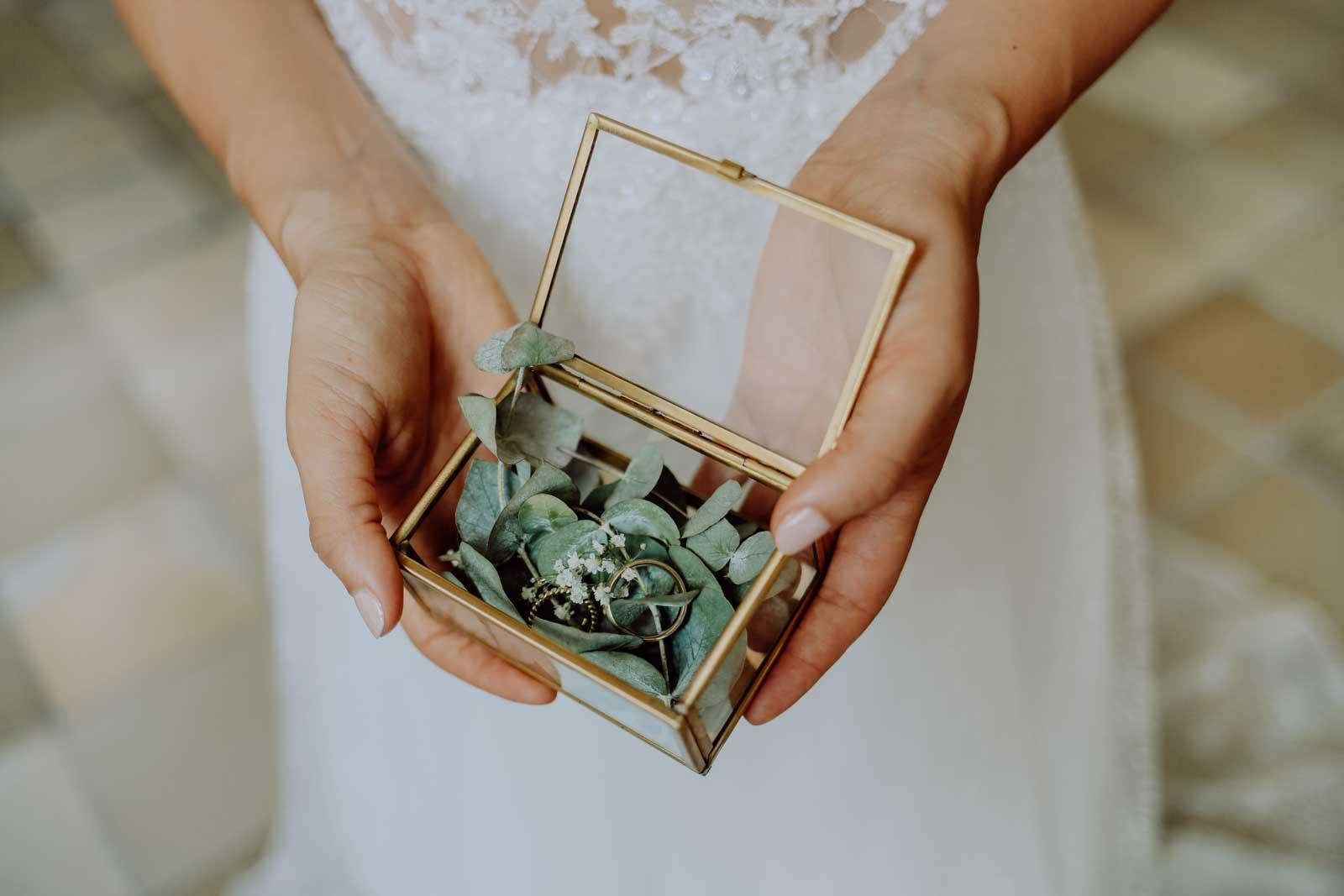 Frau hält Eheringe in ihrer Hand