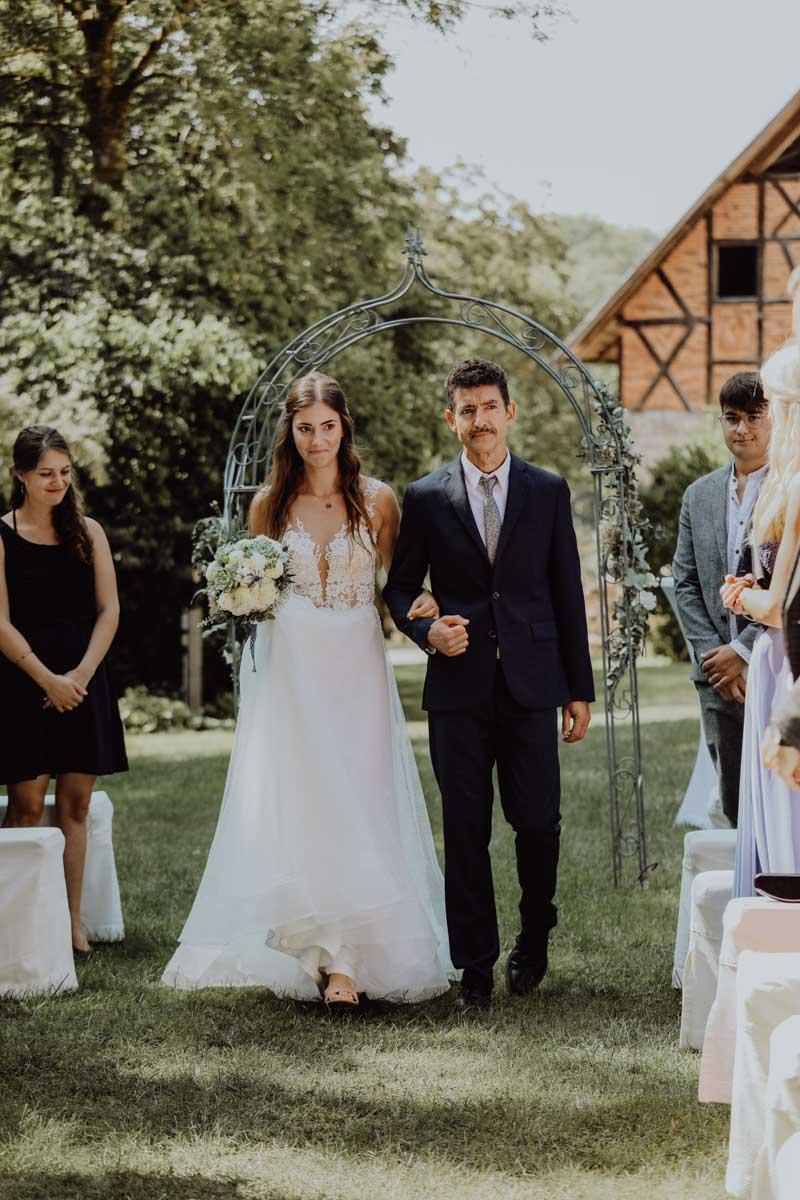 Braut läuft mit Vater über eine Wiese