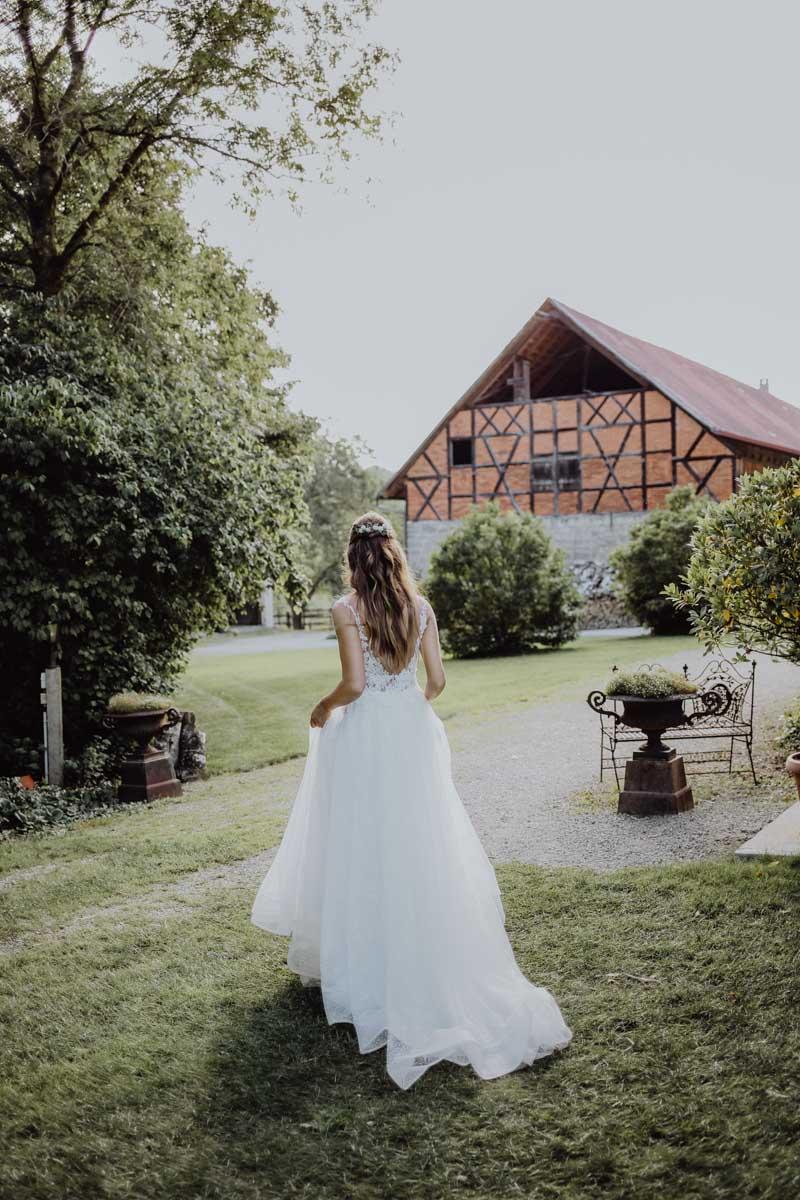 Braut hebt ihr Kleid und läuft zu einer Scheune