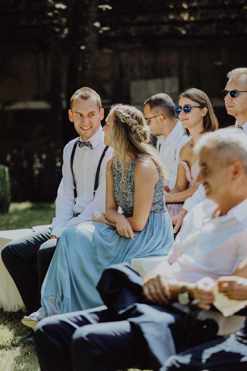 Frau mit blauem Kleid schaut Mann mit Fliege an