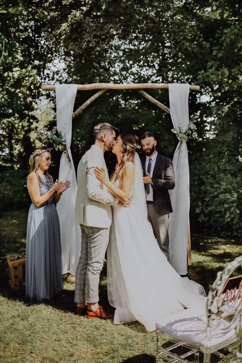 Frau im Brautkleid küsst einen Mann vor Traubogen