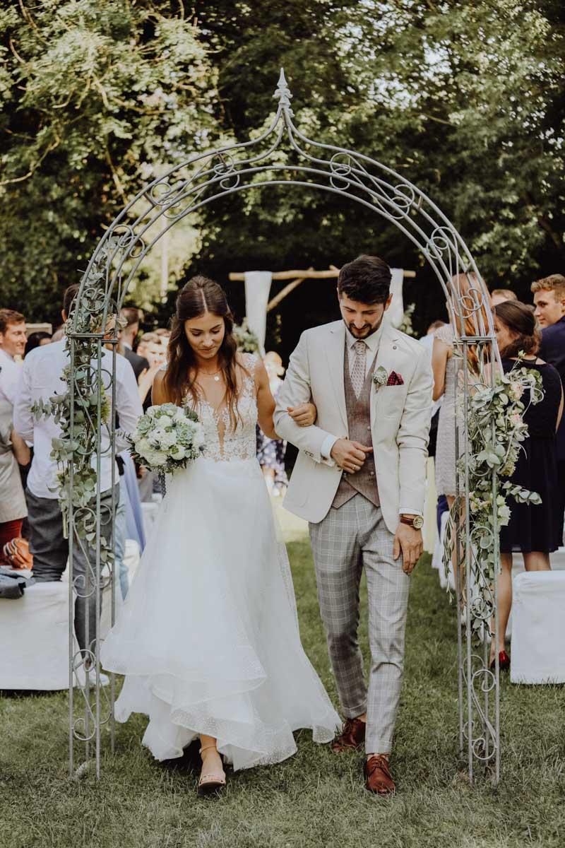 Brautpaar läuft durch einen Traubogen