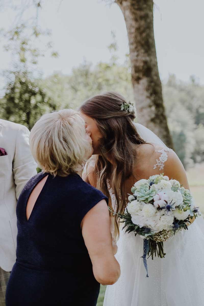 Eine Frau mit blauem Kleid küsst Braut mit Brautstrauß