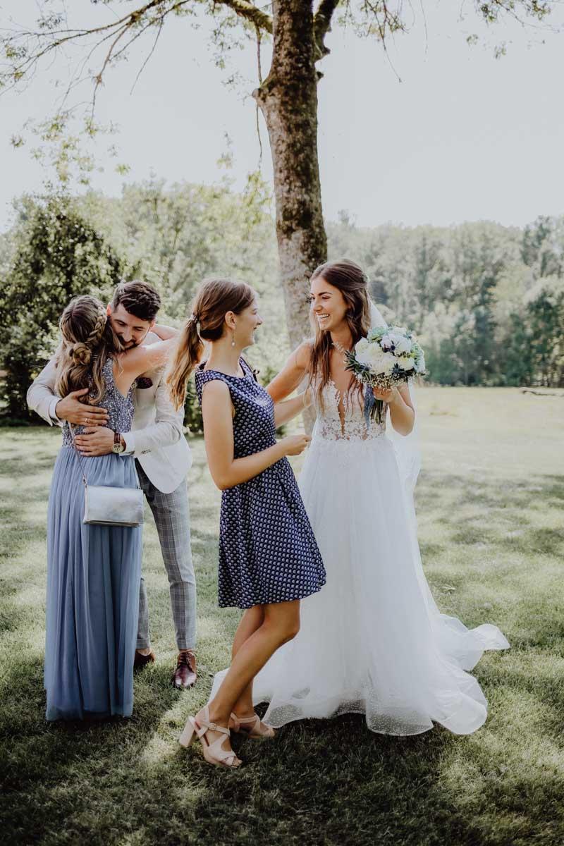 Mann umarmt Frau mit blauem Kleid und Braut hält Brautstrauß in der Hand
