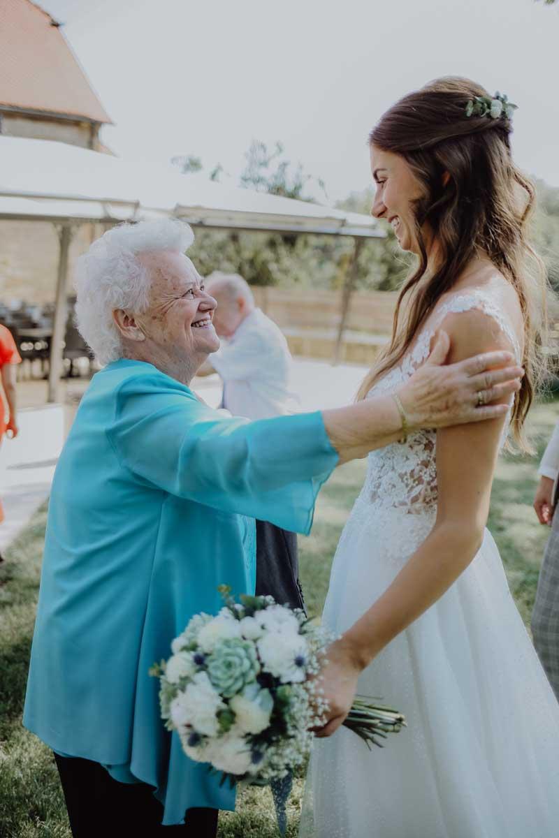 Oma mit blauer bluse schaut Braut an und lacht