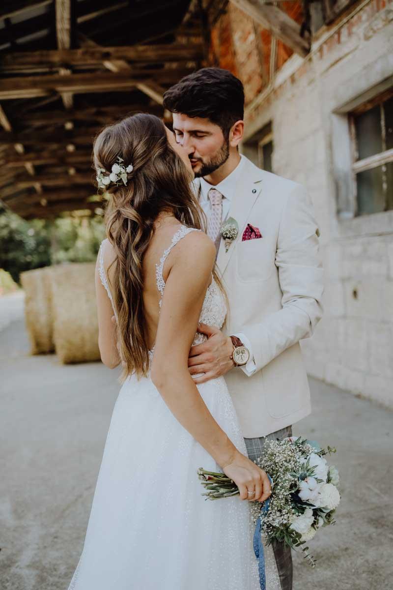 Küssendes Brautpaar vor Strohballen