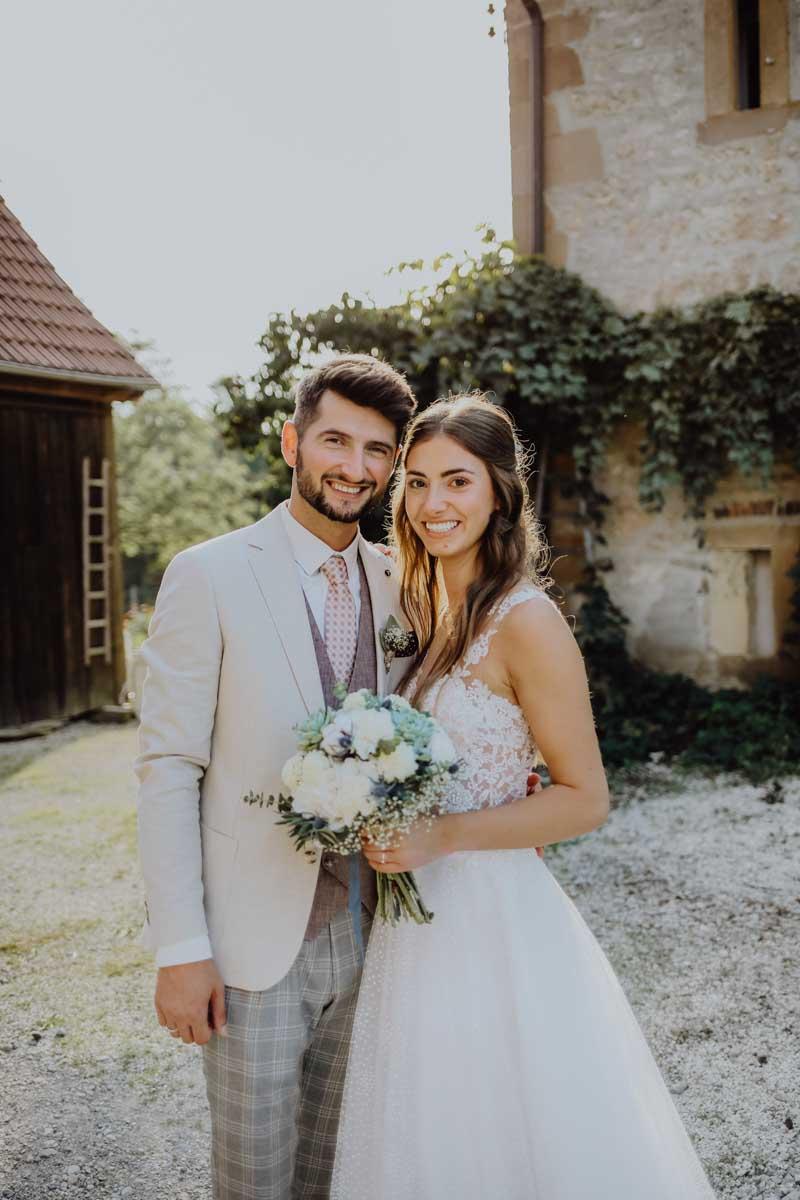 Mann und Frau mit weißem Braustrauß vor Scheune