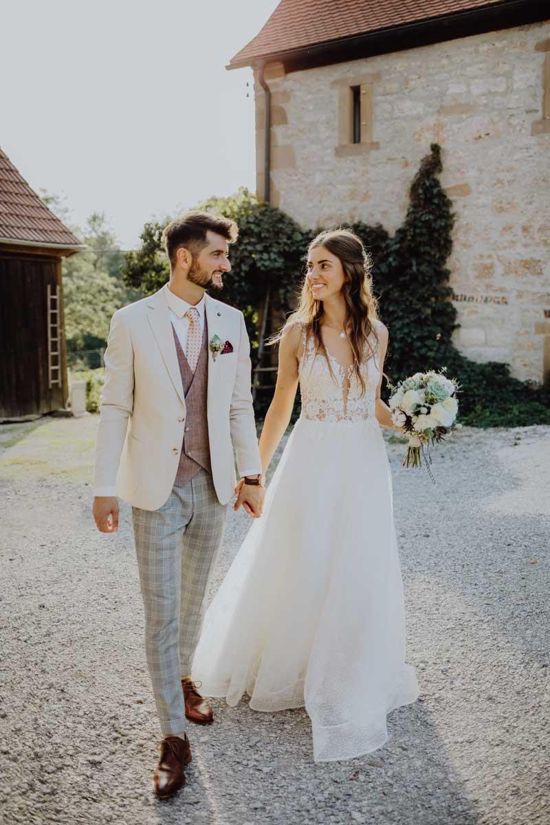 Bräutigam und Braut laufen Hand in Hand über einen Schotterweg