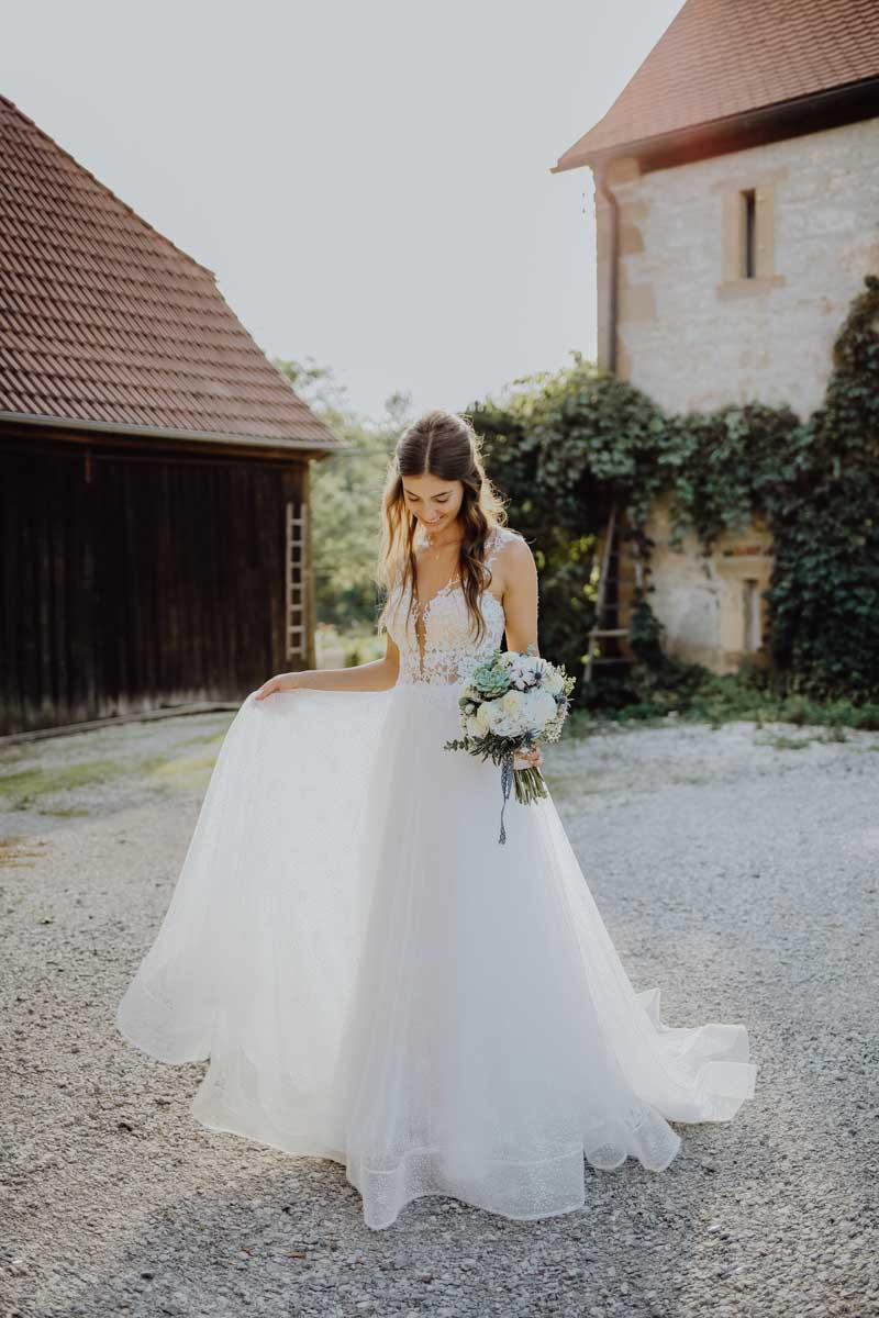 Braut hält ihr Brautkleid und Brautstrauß in der Hand