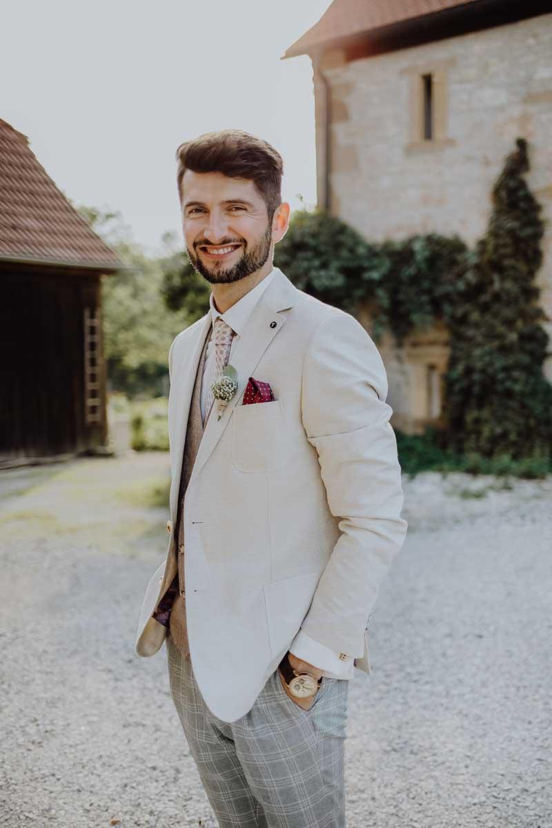 Mann im Anzug mit Anstecker und Armbanduhr