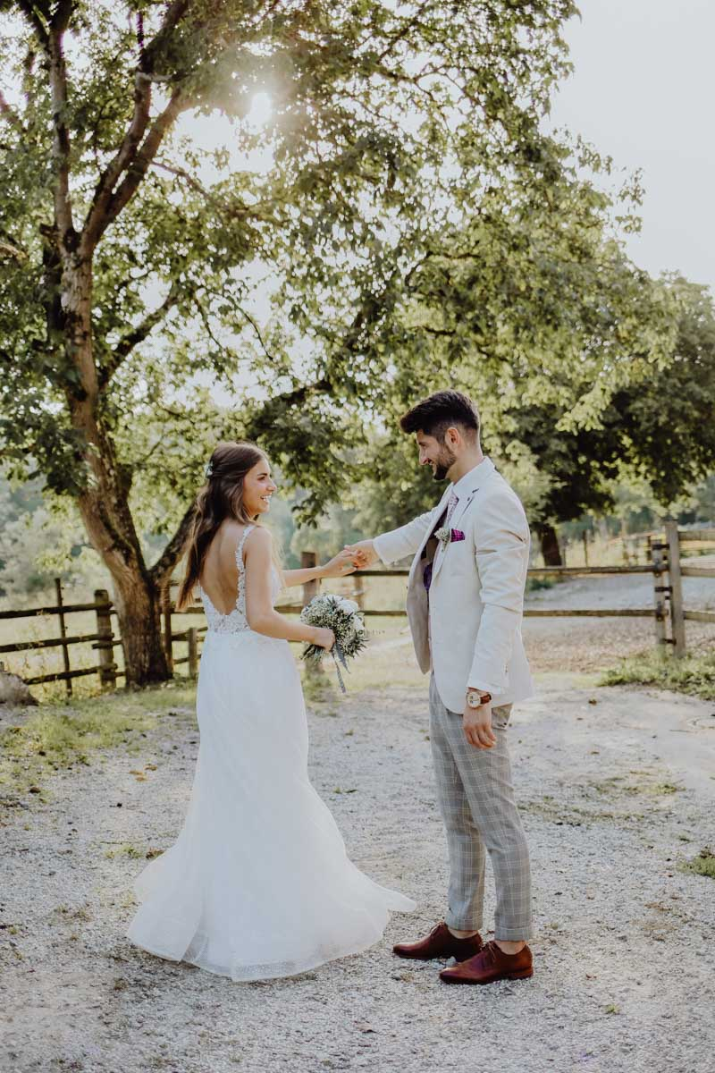 Tanzendes Brautpaar vor einem Baum und Zaun