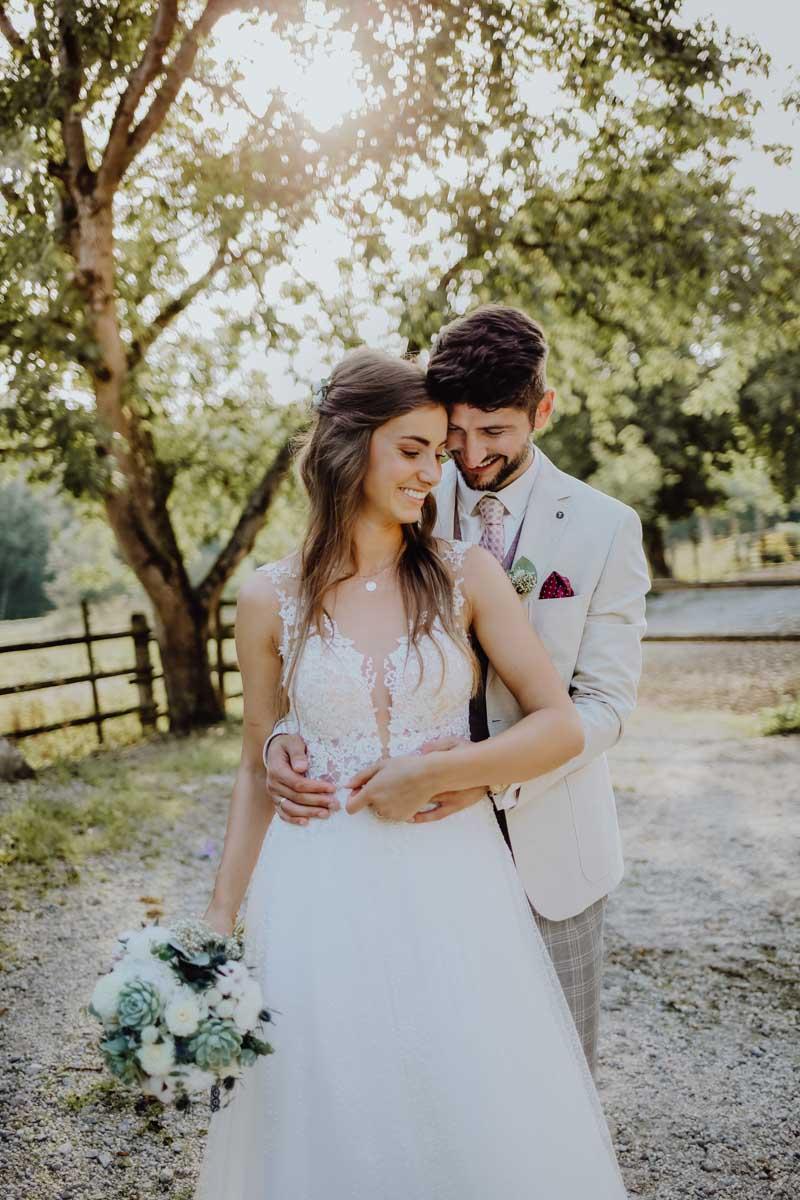 Brautpaar steht mit Braustrauß vor einem Baum
