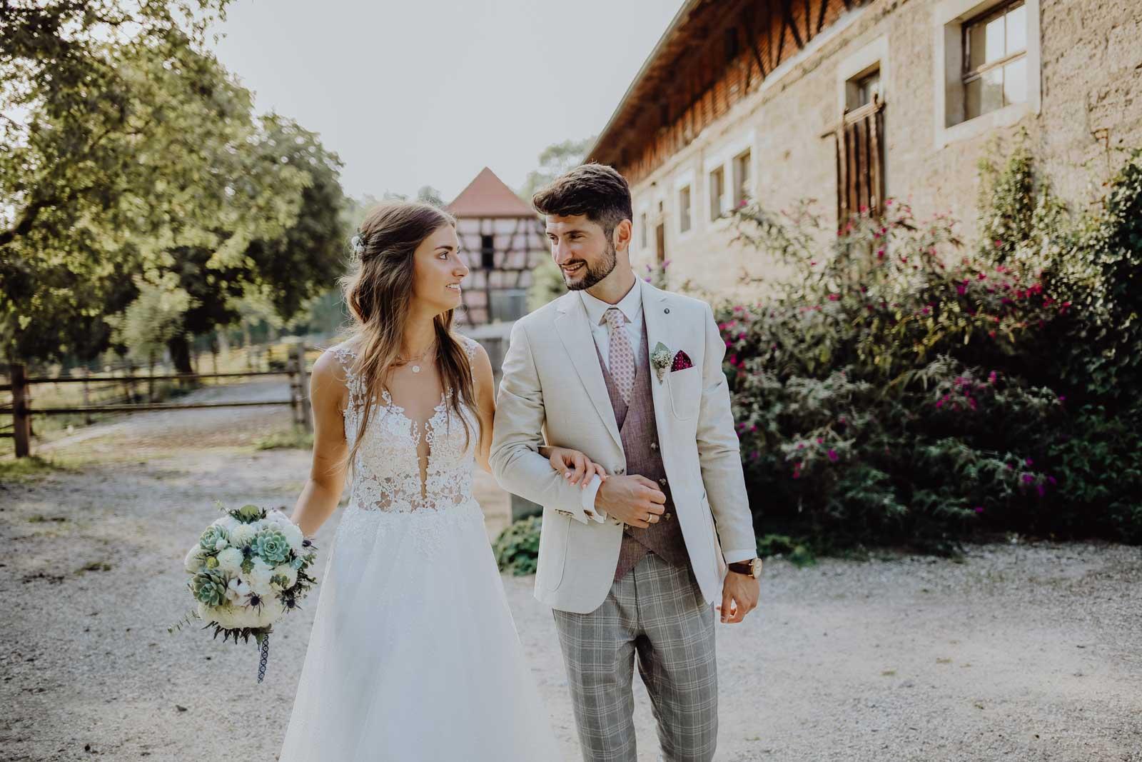 Brautpaar läuft mit Brautstrauß vor einer Scheune