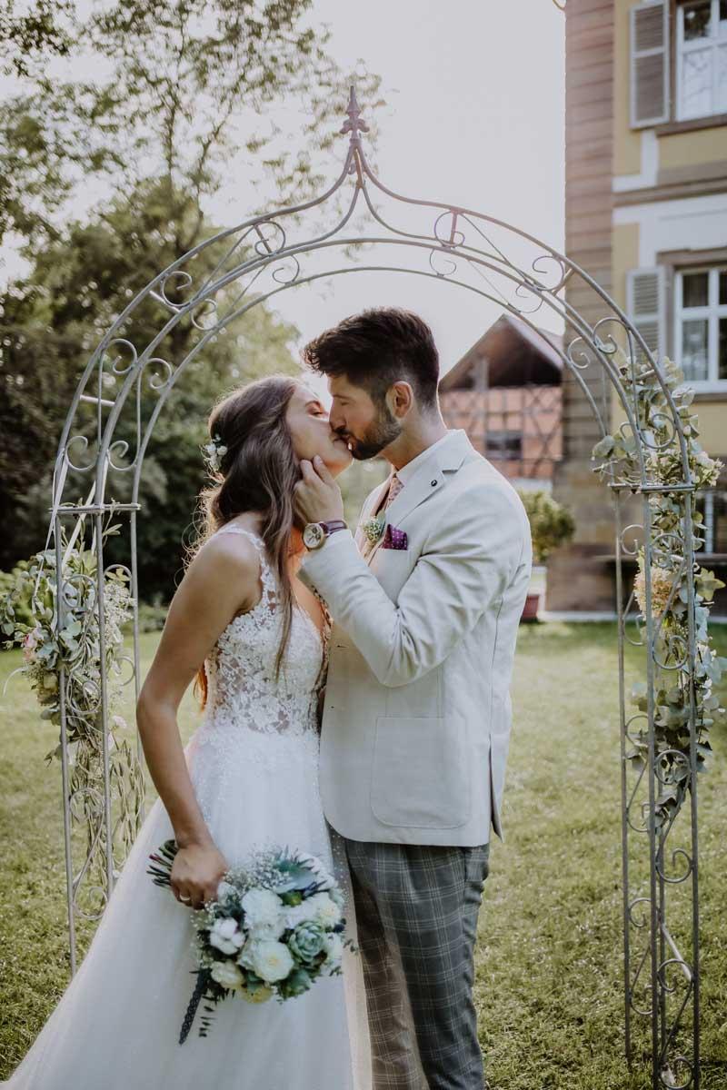 Küssendes Brautpaar steht in einem Traubogen