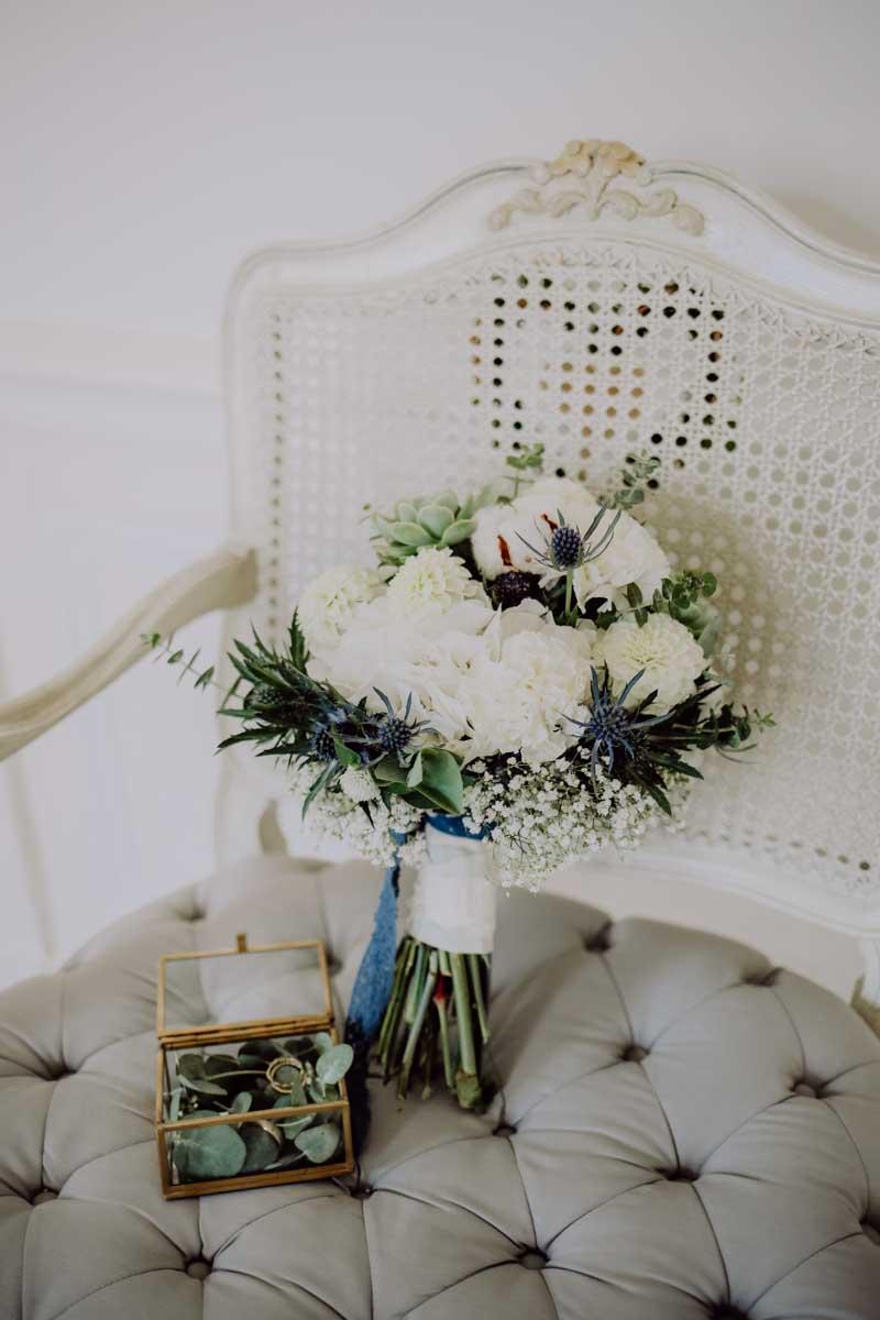 Brautstrauß und Eheringe auf Stuhl