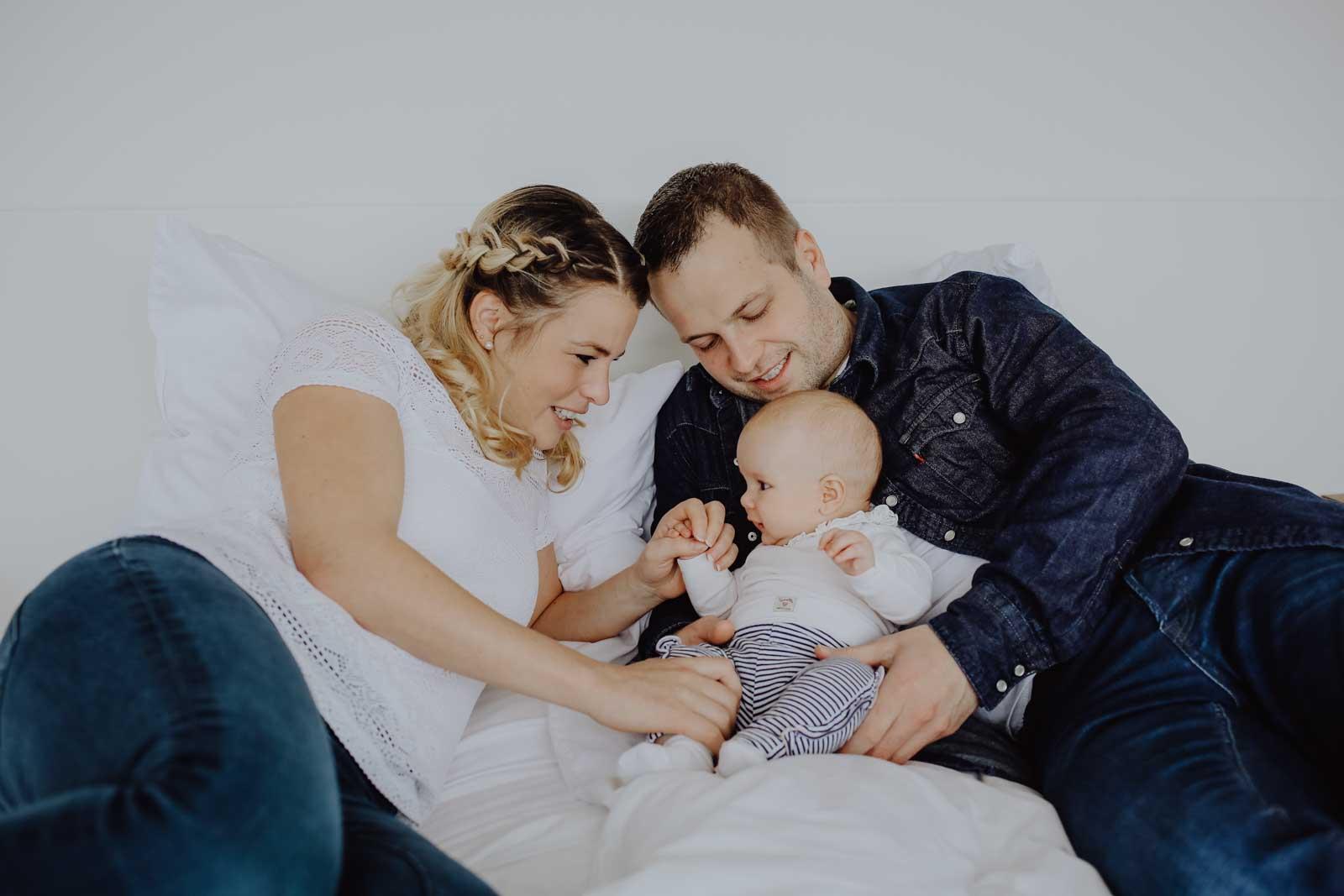 Eltern mit Baby auf Bett