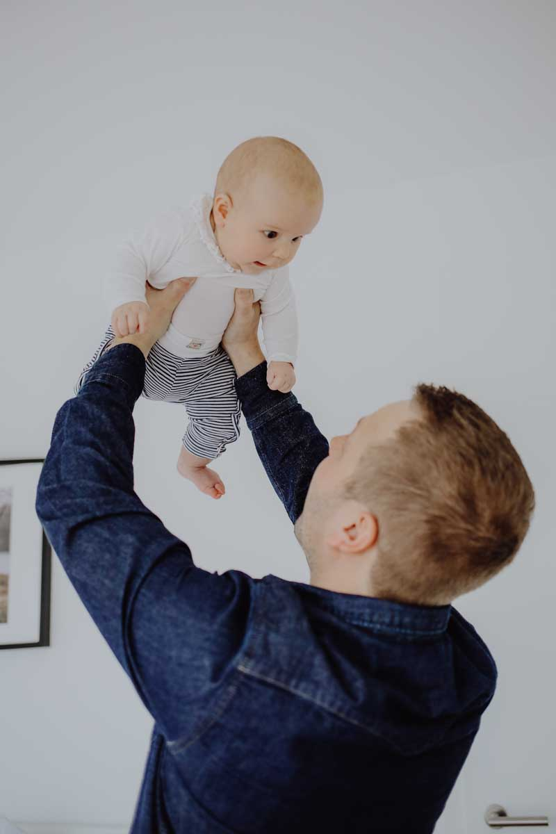 Vater hält Baby in die Luft