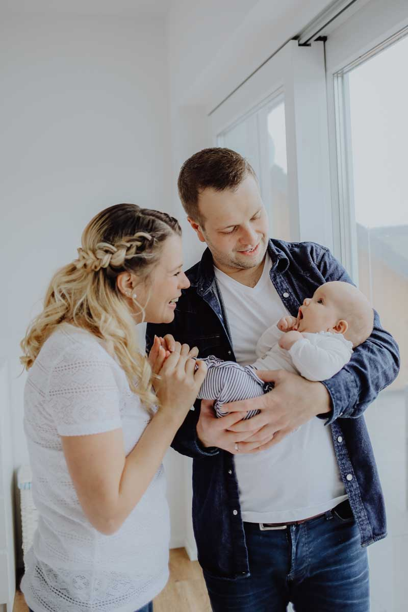 Familie steht mit Baby am Fenster