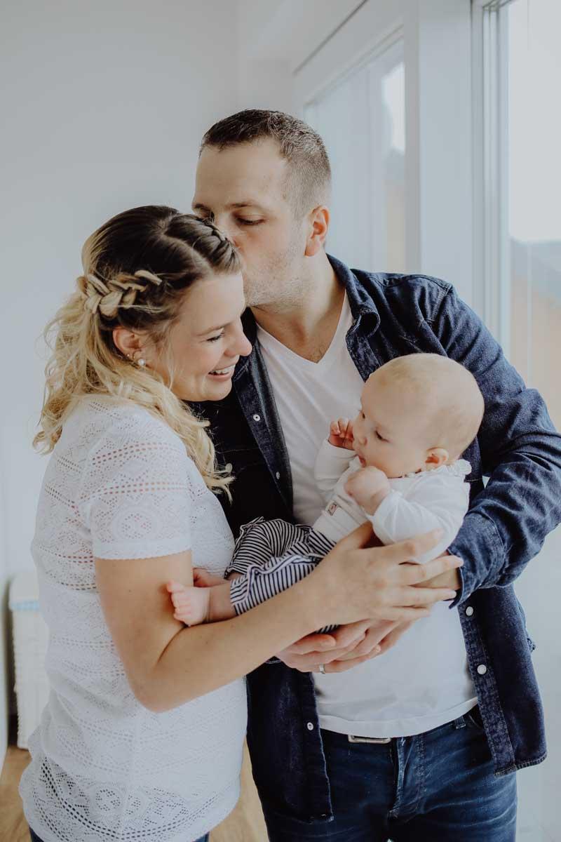 Mann gibt Frau Kuss auf die Stirn und hält Baby in der Hand