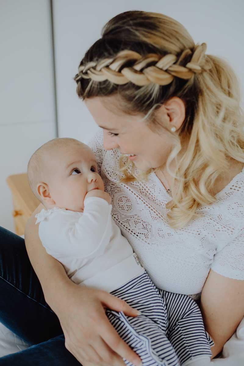 Baby mit gestreifter Hose schaut seine Mama an