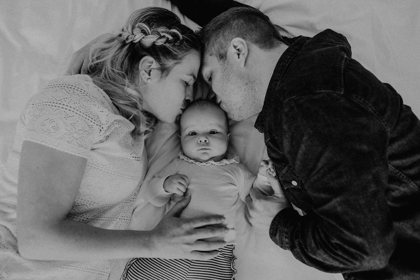 Eltern geben ihrem Baby einen Kuss auf den Kopf