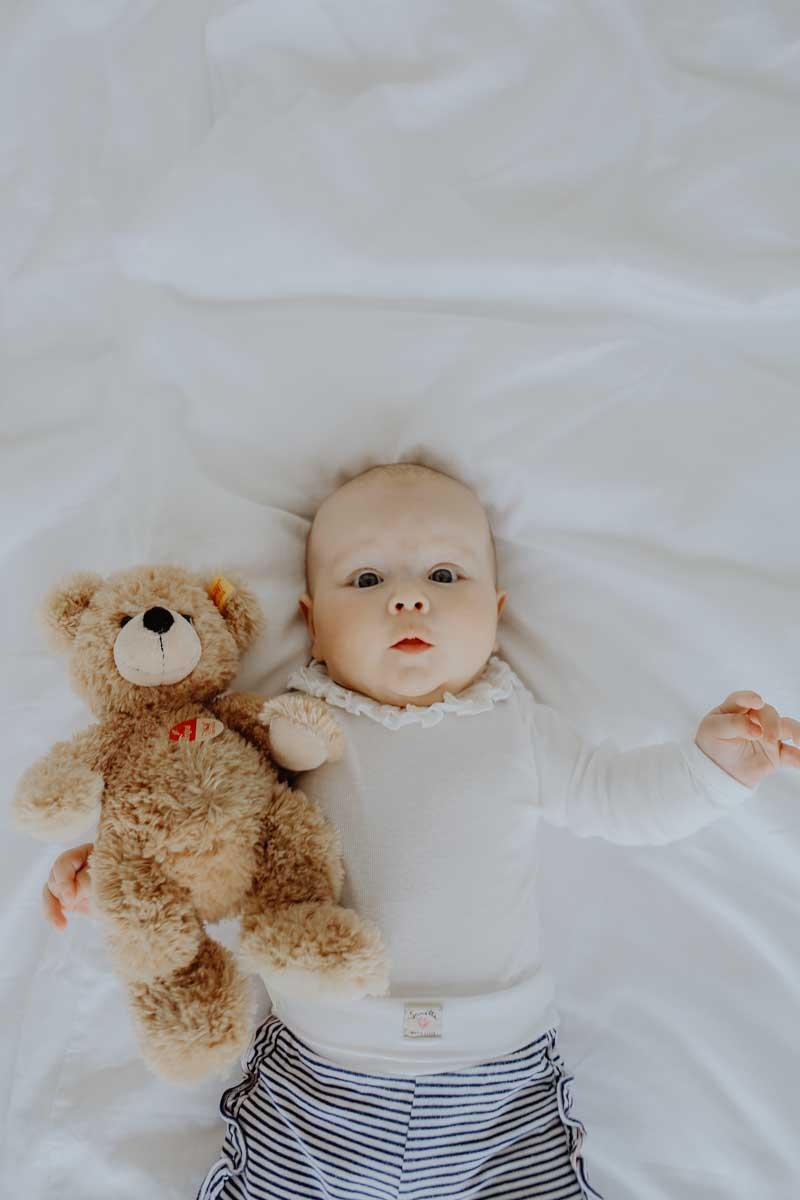 Baby hält Kuscheltier im Arm