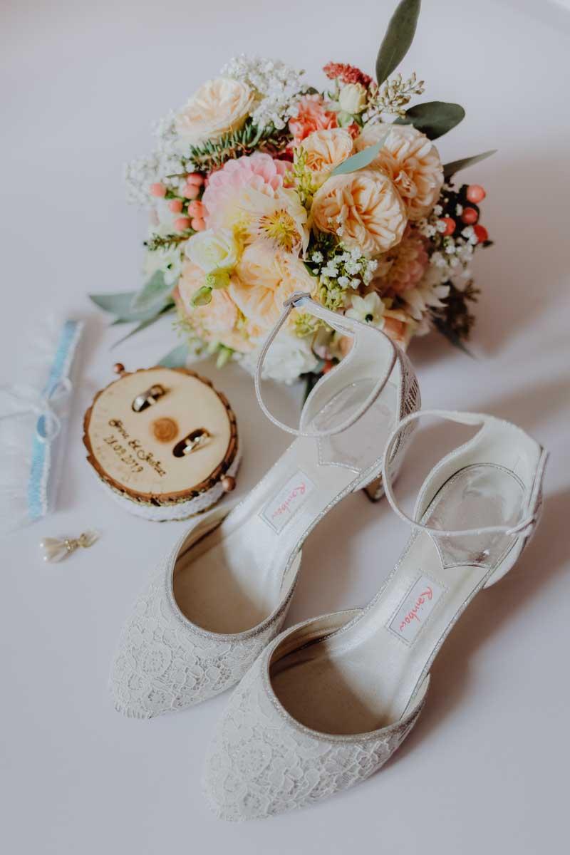 Brautschuhe mit Brautstrauß und Eheringe