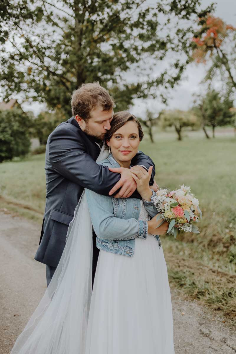 Mann umarmt Frau mit Brautstrauß