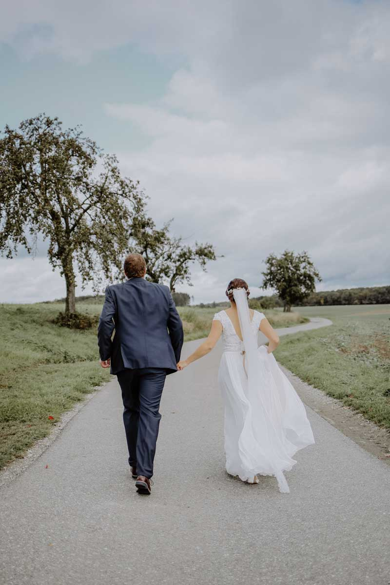 Brautpaar rennt auf einem Feldweg entlang