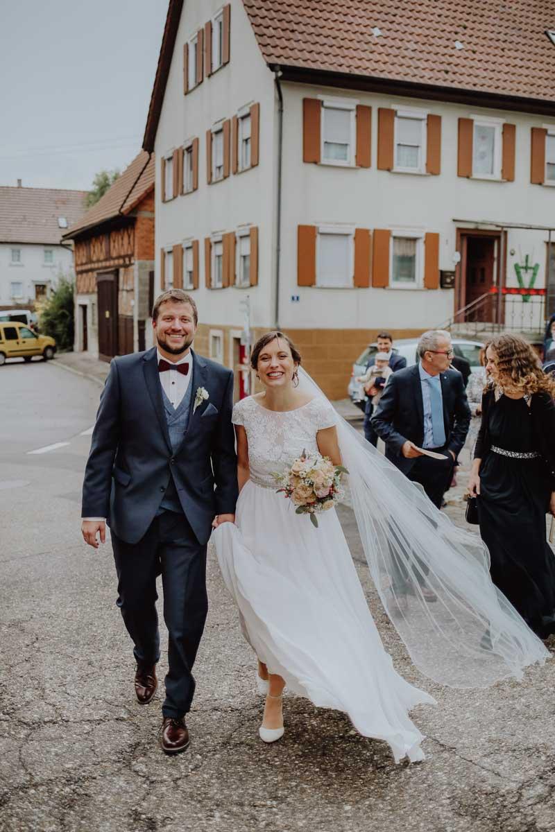 Fröhliches Brautpaar vor einem Haus