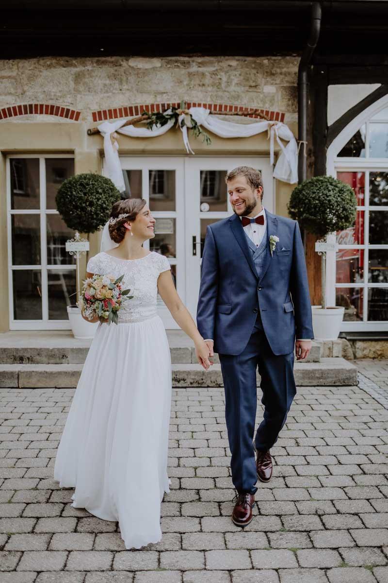 Braut und Bräutigam gehen Hand in Hand