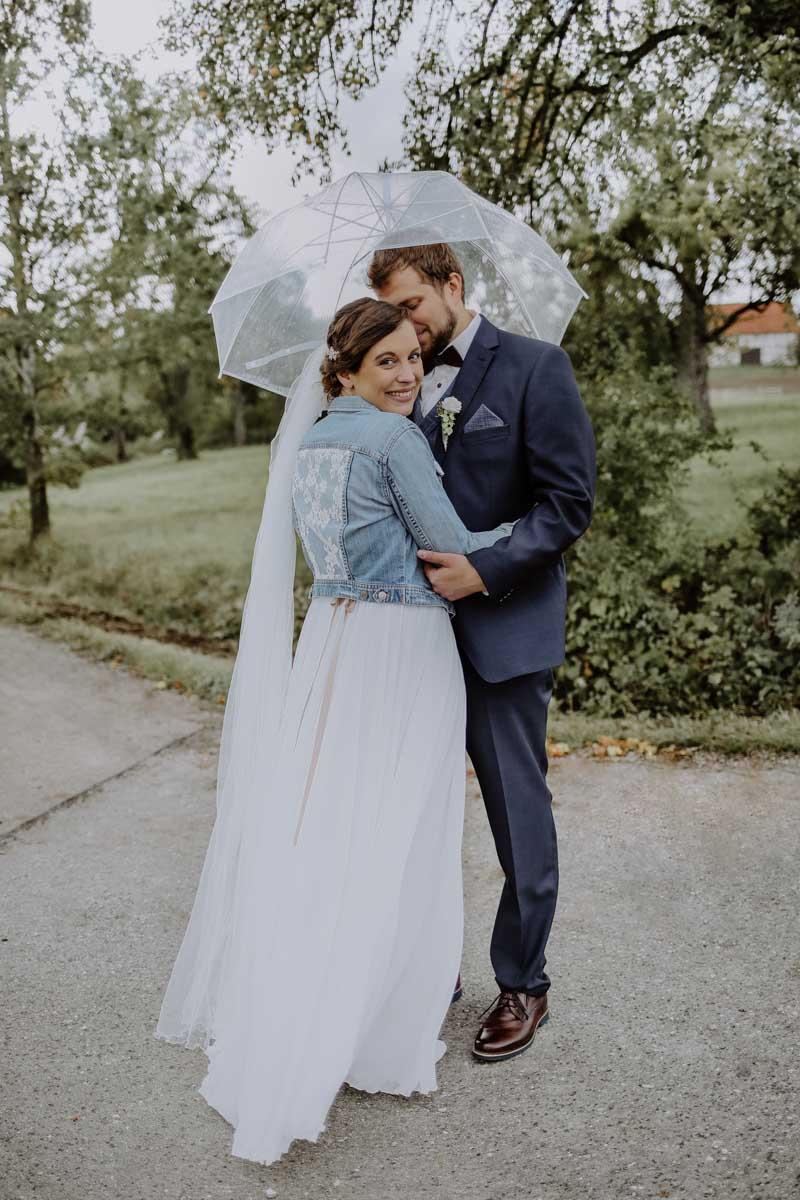 Brautpaar steht unter dem Regenschirm