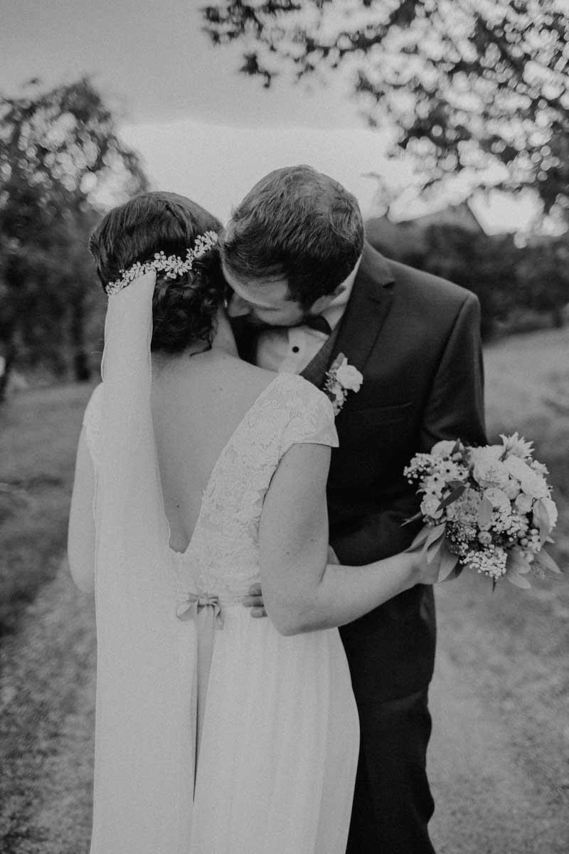 Bräutigam küsst seine Braut am Hals