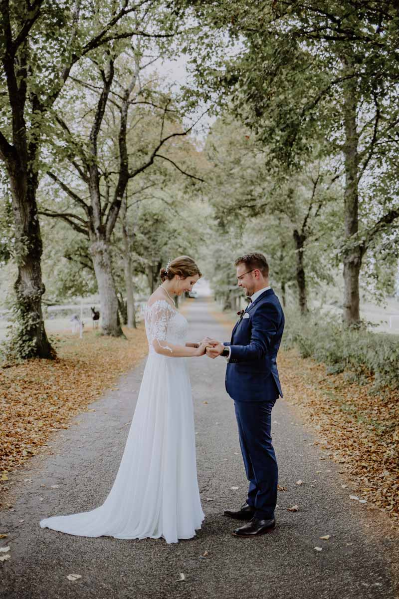Mann und Frau begutachten sich auf einer Baumallee