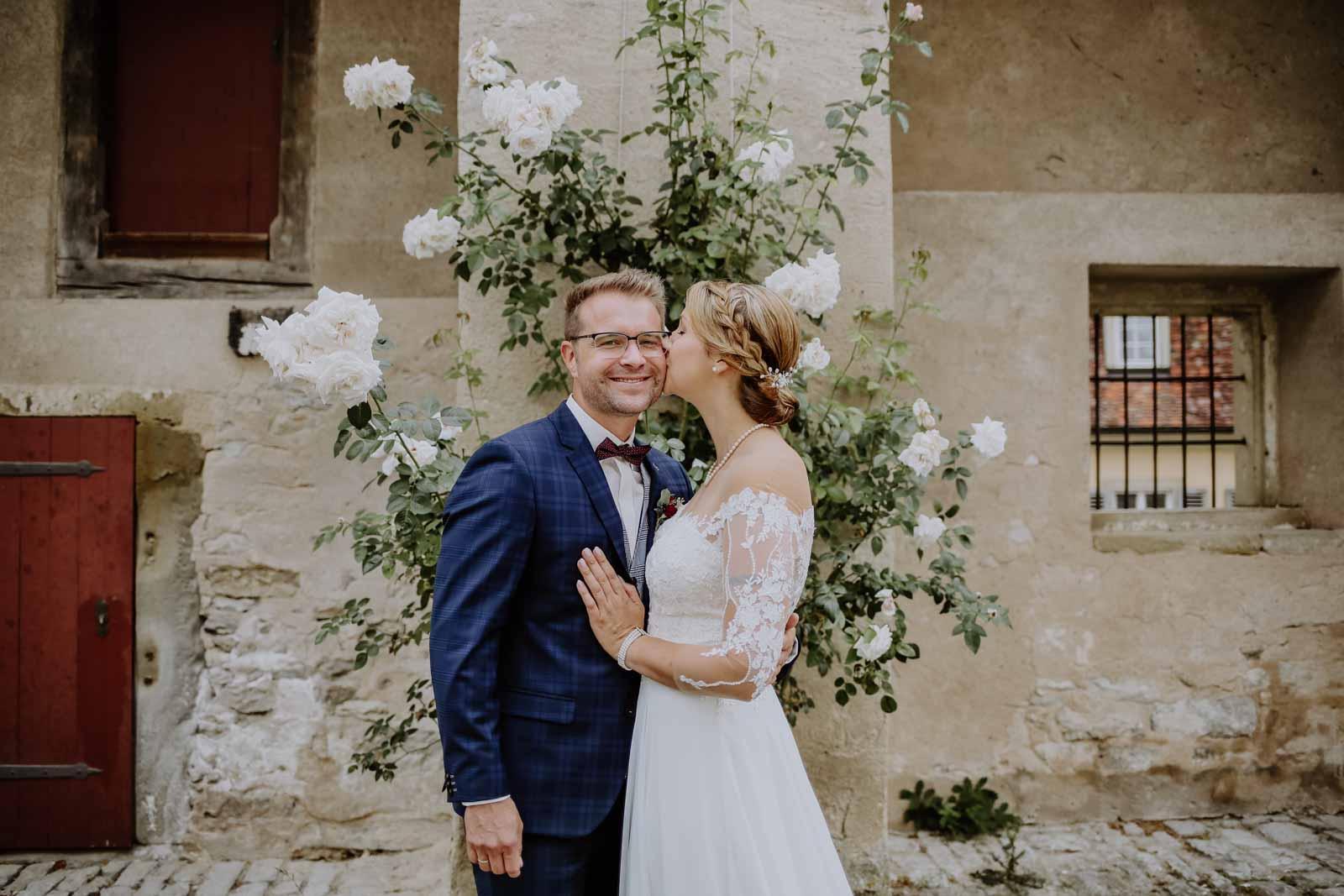 Brautpaar steht vor weißem Rosenbusch