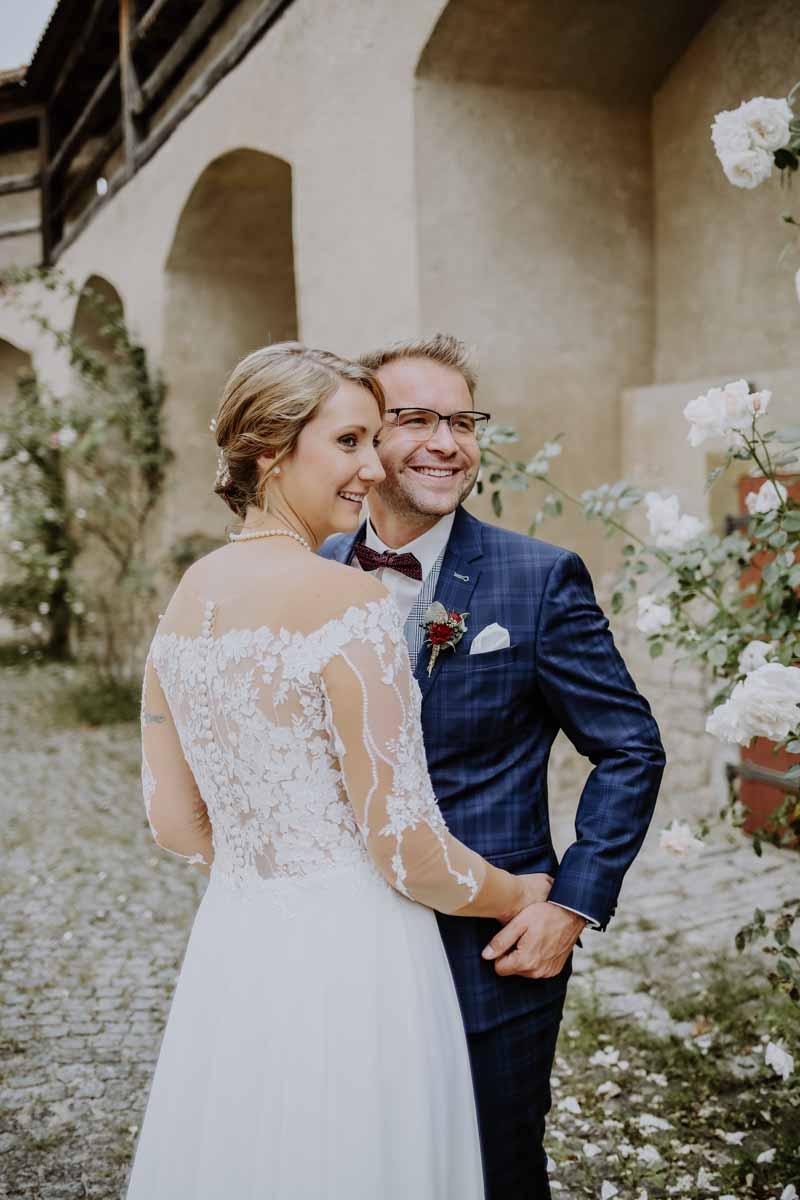 Braut umarmt Bräutigam mit blauem Anzug
