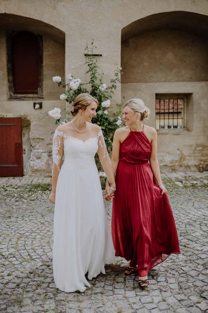 Zwei Frauen lachen vor einem Rosenbusch