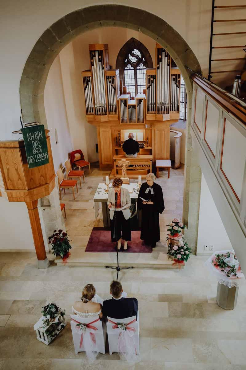 Pfarrerin steht vor dem Altar und traut Paar