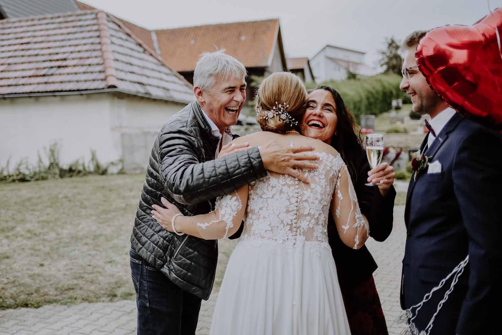 Braut wird umarmt von Mann und Frau mit Sektglas