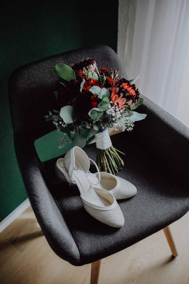 Brautschuhe und Brautstrauß auf einem Sessel