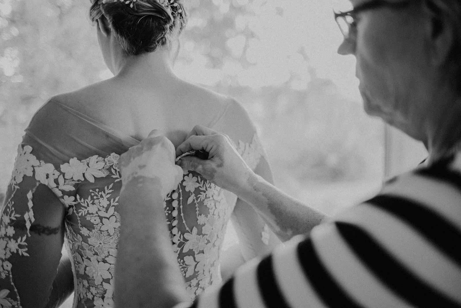 Eine Frau schließt das Kleid der Braut