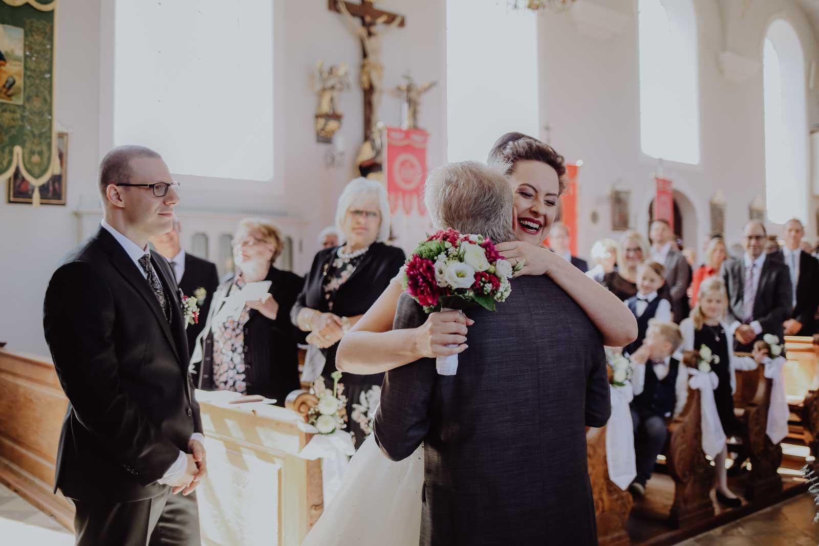 Braut umarmt einen Mann in der Kirche