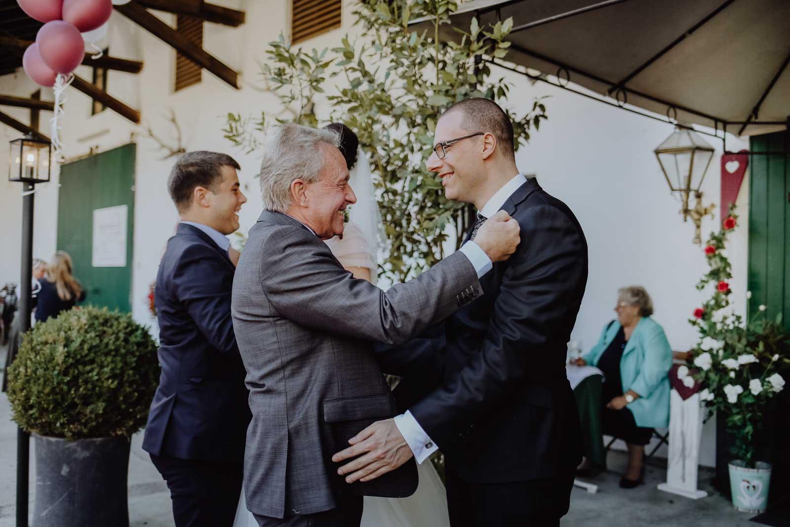Brautvater und Bräutigam umarmen sich