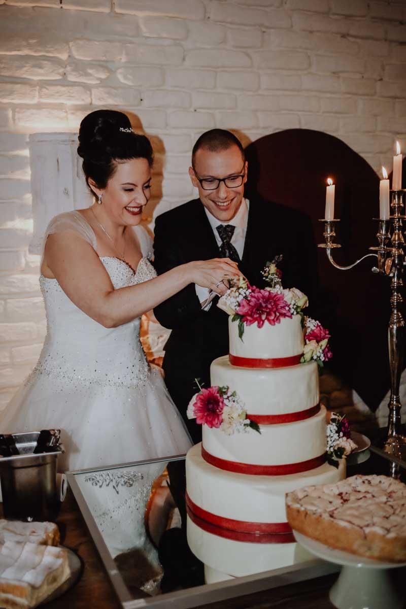 Brautpaar schneidet weisse Torte an
