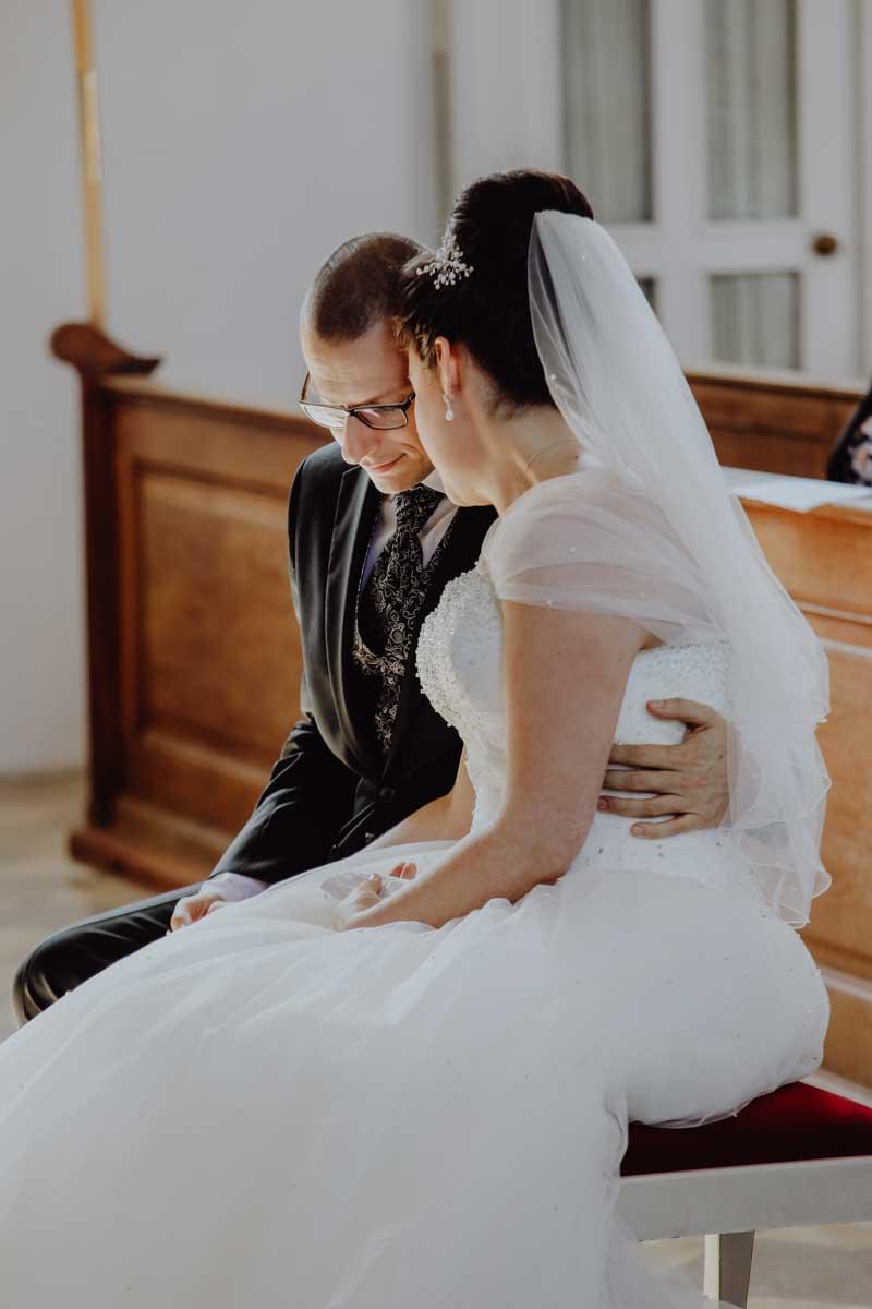 Brautpaar sitzt auf einer roten Bank