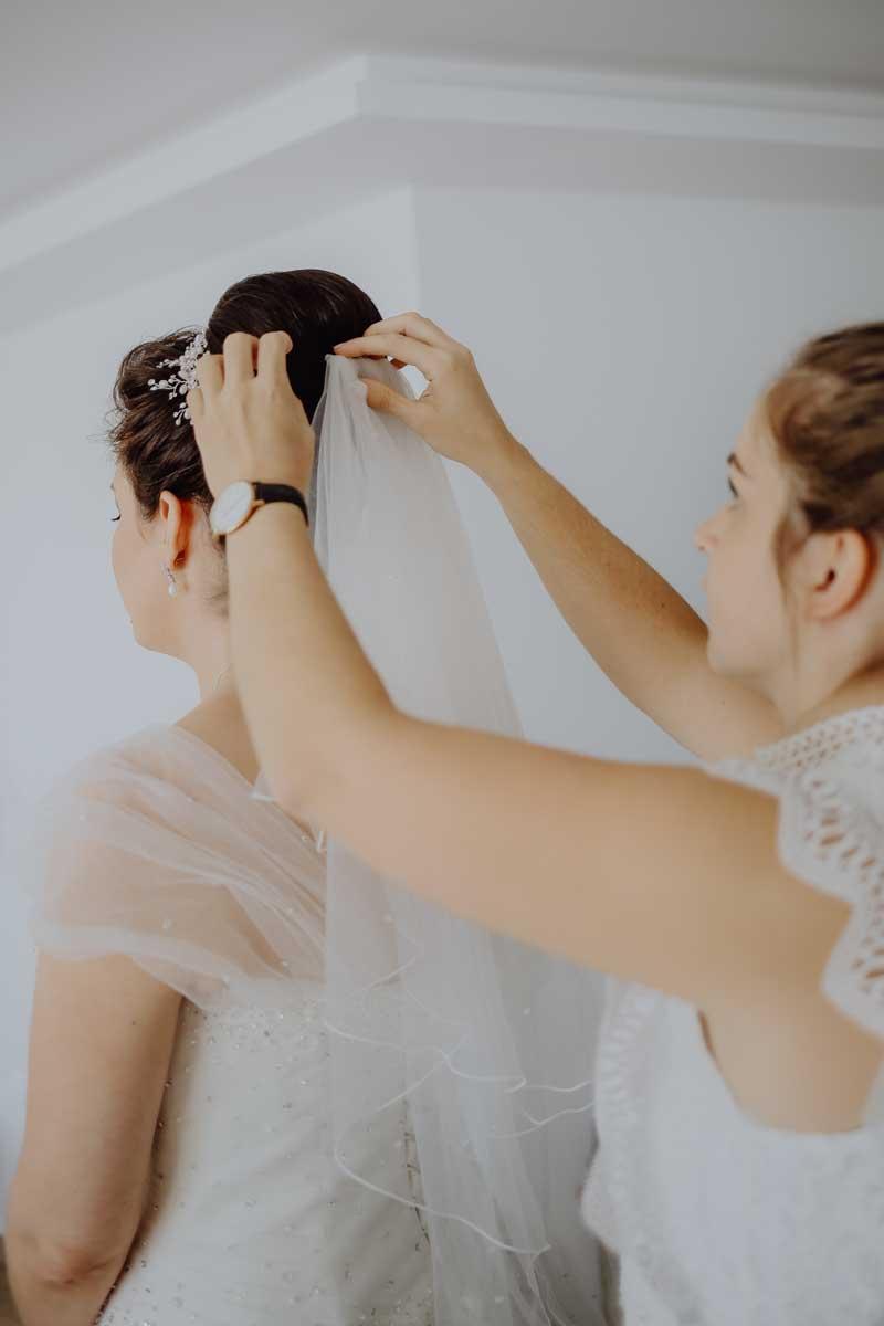 Brautschleier wird an der Braut befestigt